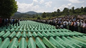 Bosnian people pray near coffins of Srebrenica victims, during amass funeral in Potocari 120 km northeast of Sarajevo, Bosnia, on Sunday, July 11, 2010. Weeping among endless rows of coffins, tens of thousands gathered Sunday in the eastern Bosnian town of Srebrenica to bury hundreds of massacre victims on the 15th anniversary of the worst crime in Europe since the Nazi era. (AP Photo/Amel Emric)